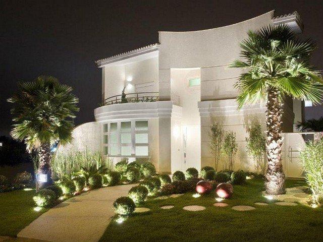 Entrada iluminada e com palmeiras